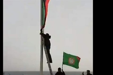 A group of Shiite protesters taking down the Libyan flag