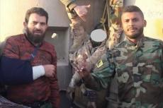 Wanis Bu Khamada's son (R) posing with Jalal al-Makhzoum's hanged corpse outside Al-Saiqa camp